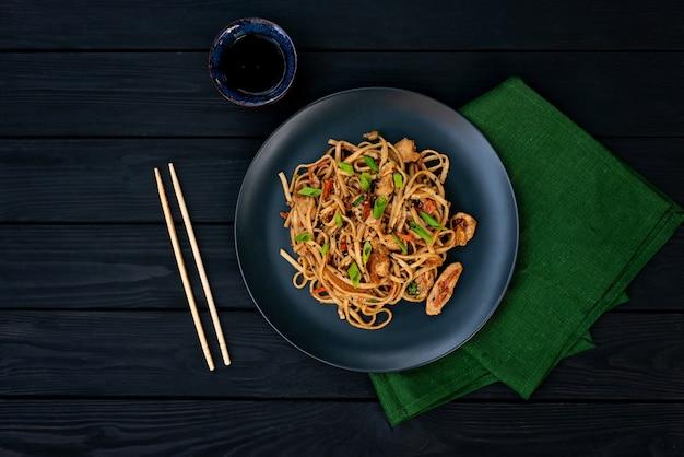 Tagliatelle asiatiche di udon con verdure di pollo e salsa teriyaki su un fondo di legno nero