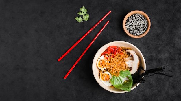 Tagliatelle cinesi in padella con verdure e uova su sfondo nero strutturato