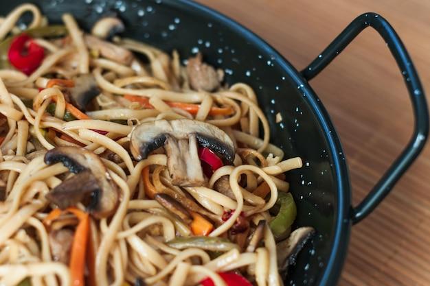 Tagliatelle con alcune verdure come zenzero, cipolla, pepe e funghi, condite con salsa di soia