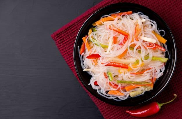 Tagliatelle con verdure su uno sfondo nero accanto a peperoncino.