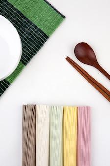 Tagliatelle coreane con cucchiaio e bacchette di legno