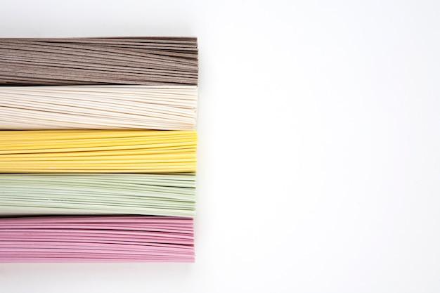 Tagliatelle coreane in cinque colori su sfondo bianco