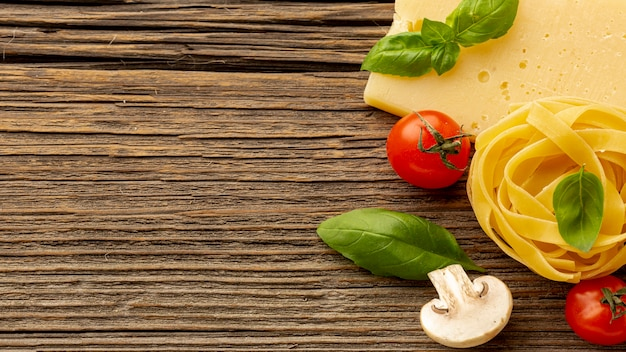 Tagliatelle crude con foglie di basilico pomodori a pasta dura e copia spazio