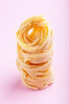 Tagliatelle crude crude pasta su uno sfondo rosa pastello