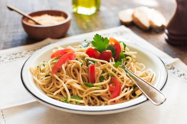 Tagliatelle deliziose cucinate sul piatto bianco sopra il placemat