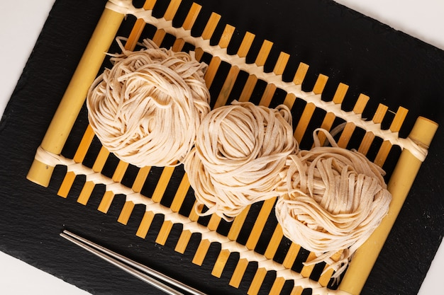 Tagliatelle dell'uovo orientali casalinghe dell'alimento asiatico sul vassoio di bambù