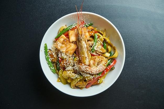 Tagliatelle di grano ramen con cozze, gamberi e verdure fritte in un wok in una ciotola bianca
