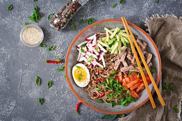 Tagliatelle di grano saraceno con carne di manzo, uova e verdure. cibo coreano. zuppa di pasta di grano saraceno. vista dall'alto. disteso