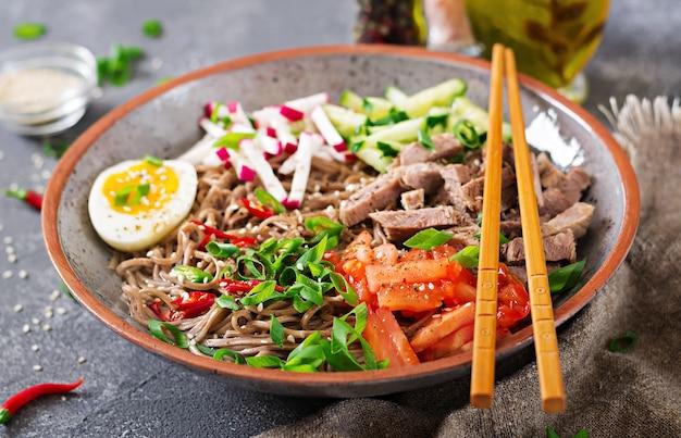 Tagliatelle di grano saraceno con carne di manzo, uova e verdure. cibo coreano. zuppa di pasta di grano saraceno.