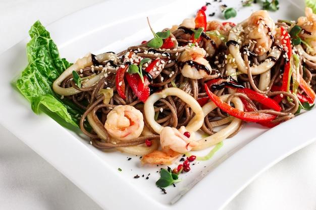 Tagliatelle di grano saraceno soba con frutti di mare, verdure fresche e salsa di soia, cucina asiatica