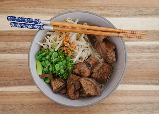 Tagliatelle di maiale a lenta cottura con funghi shiitake e verdure miste o brodo di maiale brasato.