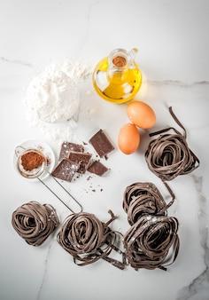 Tagliatelle di pasta al cioccolato grezza non preparate, con ingredienti per cucinare