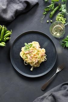 Tagliatelle di pasta con panna, piselli e pancetta. delizioso pranzo mediterraneo.