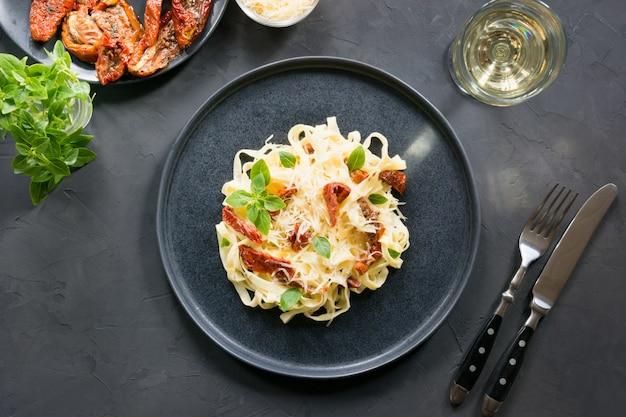 Tagliatelle di pasta con pomodori secchi e origano sul nero. delizioso pranzo mediterraneo.