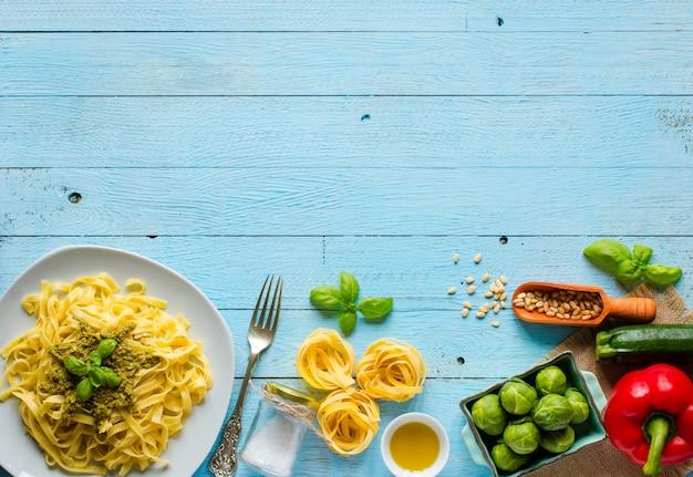 Tagliatelle di pasta con salsa al pesto e altre verdure su uno sfondo di legno. vista dall'alto