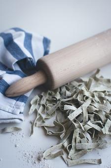 Tagliatelle di pasta coperte di farina con un rullo di legno su uno sfondo bianco
