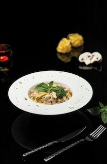 Tagliatelle di pasta in salsa di panna con foglie di basilico.