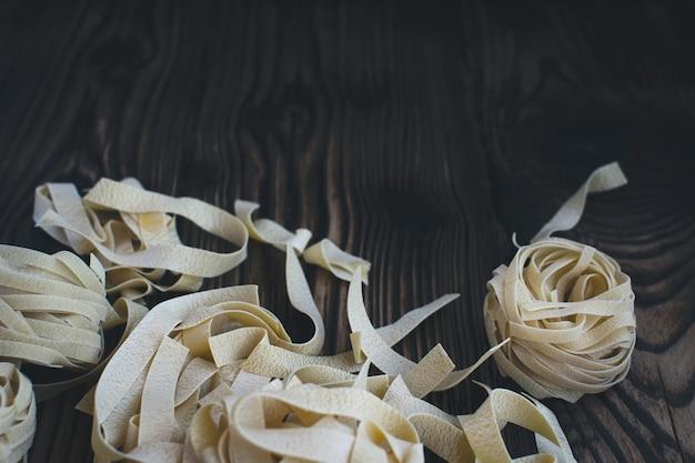 Tagliatelle di pasta su un fondo di legno