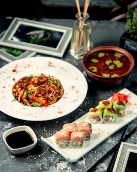 Tagliatelle di pollo sul tavolo con involtini di sushi