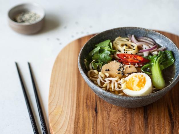 Tagliatelle di ramen asiatiche con pollo, cavolo pak choi e uovo