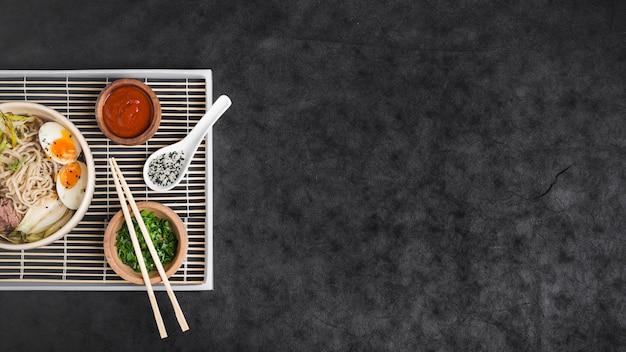 Tagliatelle di ramen asiatiche con uova e salse su placemat