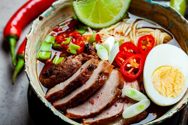 Tagliatelle di ramen piccanti asiatiche con carne di maiale, uovo e verdure in ciotola blu
