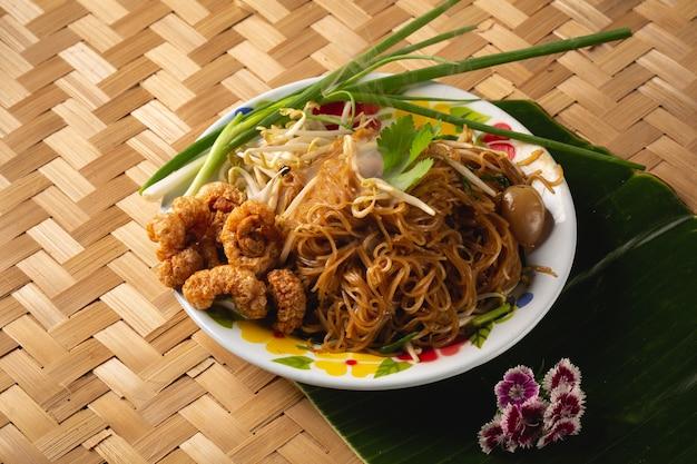 Tagliatelle di riso asiatiche con carne di maiale croccante e primo piano di verdure sul tavolo. vista dall'alto di un orizzontale