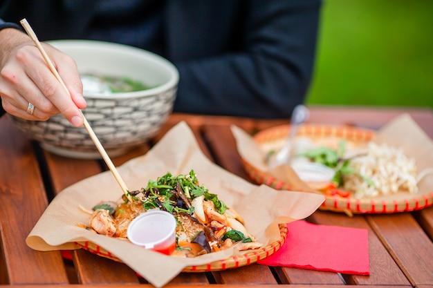 Tagliatelle di riso asiatiche con verdure e sause close-up sul tavolo