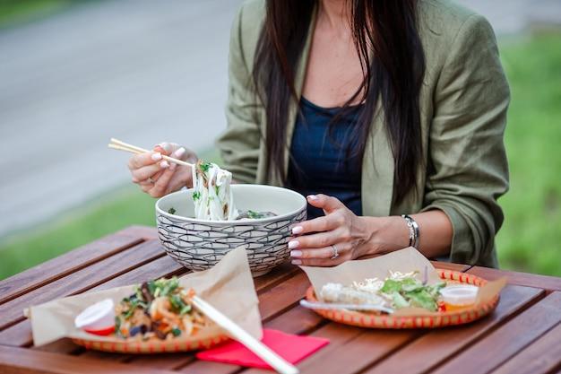 Tagliatelle di riso asiatiche con verdure e sause vicino sul tavolo