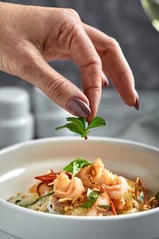 Tagliatelle di riso con gamberetti e frutti di mare, tagliatelle piccanti di stile asiatico in ciotola.