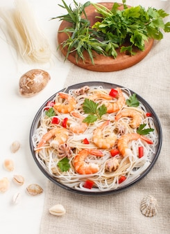Tagliatelle di riso con gamberi o gamberi e piccoli polpi sul piatto di ceramica grigia su un fondo di legno bianco