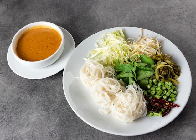Tagliatelle di riso con salsa al curry di pesce servita con verdure, kanom jeen nam ya cucina tradizionale tailandese