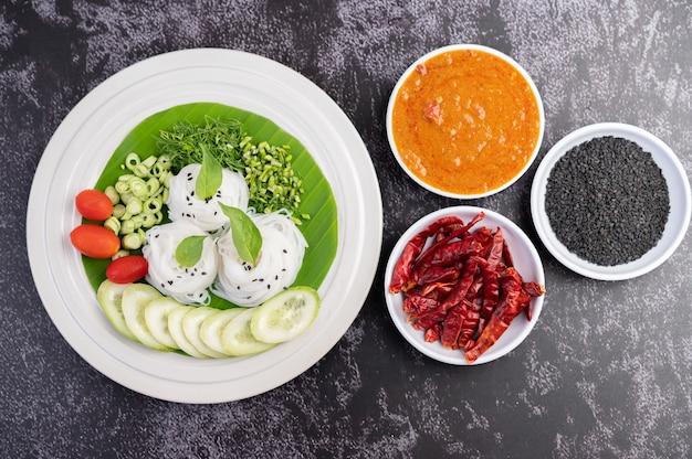 Tagliatelle di riso in una foglia di banana con verdure e contorni splendidamente posati. cibo thailandese.