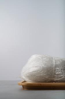 Tagliatelle di riso sottili crudi sul piatto di bambù con le bacchette sulla superficie della pietra con lo spazio della copia.