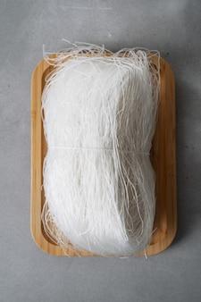 Tagliatelle di riso sottili crudi sul piatto di bambù sulla superficie della pietra con i bastoni