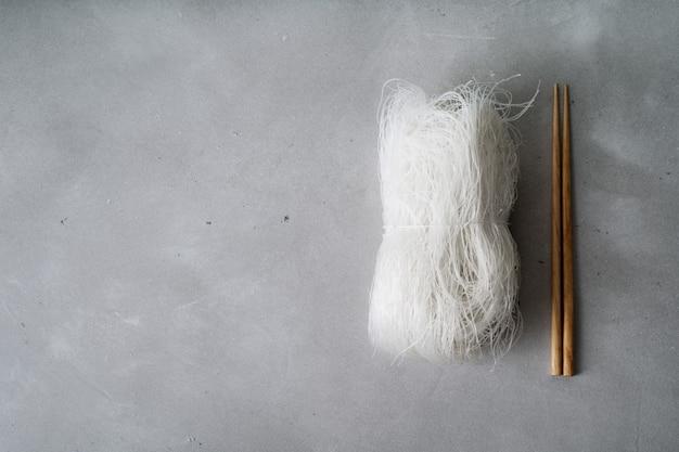 Tagliatelle di riso sottili crudi sulla superficie della pietra con le bacchette.