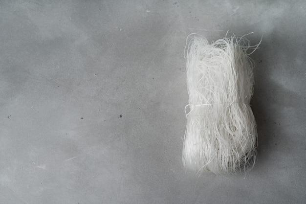 Tagliatelle di riso sottili crudi sulla superficie della pietra. flat lay con copia spazio.