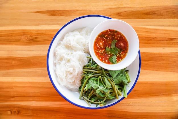 Tagliatelle di riso tailandesi con salsa di peperoncino piccante sul piatto verdura di vermicelli di riso