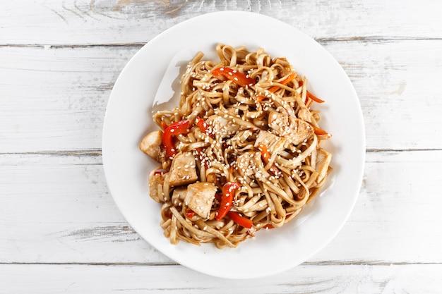 Tagliatelle di udon fritte con il pollo sulla tavola di legno. pad thai
