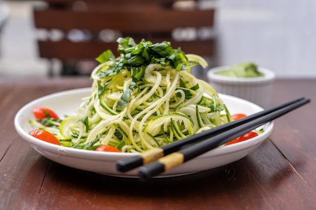 Tagliatelle di zucchine a spirale, cetriolo, pomodorini, aglio in un pesto cremoso di avocado. cibo crudo per vegetariani