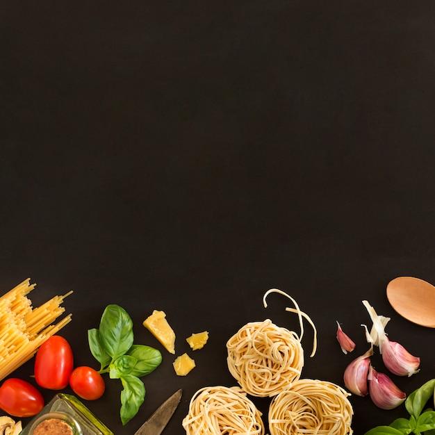 Tagliatelle e pasta degli spaghetti con gli ingredienti su fondo nero