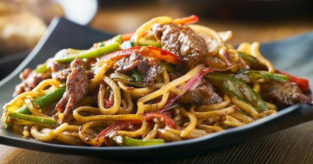 Tagliatelle fritte scalpore asiatiche con panorama di peperoni e cipolle di manzo