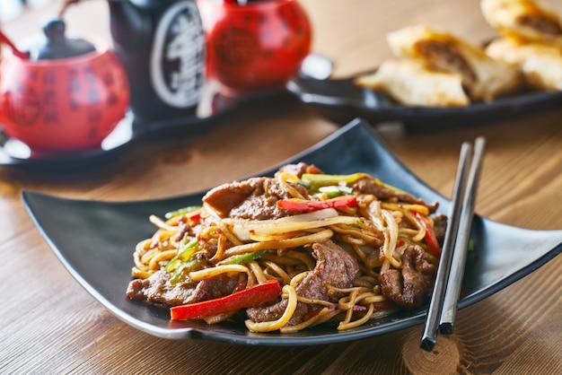 Tagliatelle fritte stir asiatiche con peperoni e cipolle di manzo