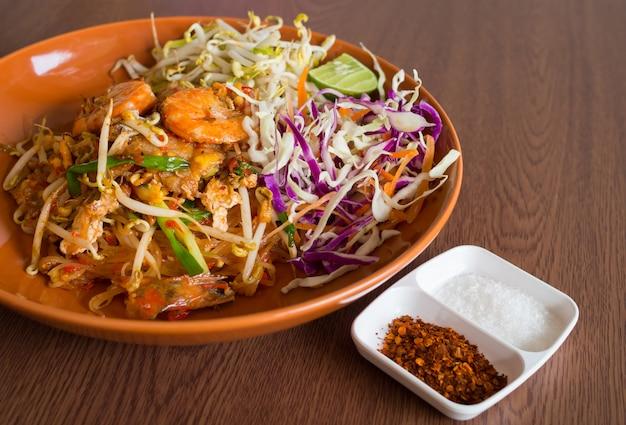 Tagliatelle fritte tailandesi con il fondo di legno della tavola delle verdure e del gamberetto