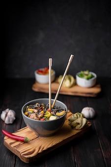 Tagliatelle in ciotola con le bacchette e l'aglio