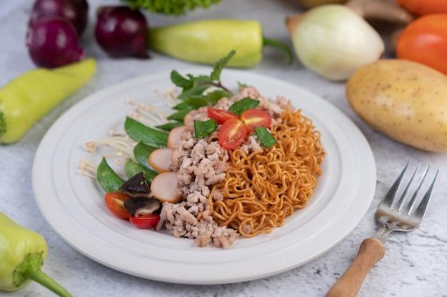 Tagliatelle in padella con carne di maiale tritata, edamame, pomodori e funghi in un piatto bianco.
