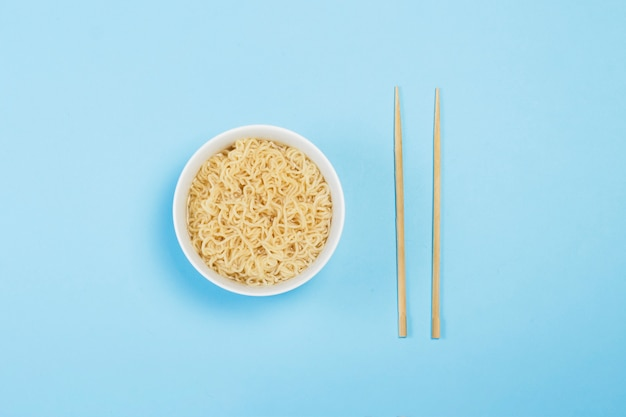 Tagliatelle istantanee asiatiche su un piatto bianco e bastoncini cinesi su una superficie blu. il concetto di cibi pronti, fast food, cibo spazzatura. vista piana, vista dall'alto.