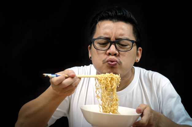 Tagliatelle istantanee mangiatori di uomini asiatici sul nero