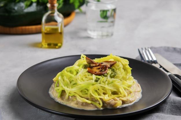 Tagliatelle o zuppa di zucchine con salsa cremosa di funghi e pesto.