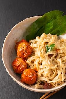 Tagliatelle orientali casalinghe dell'uovo di concetto asiatico dell'alimento e polpette piccanti in ciotola ceramica su fondo nero